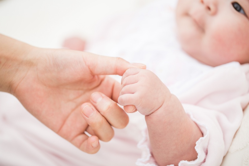 母親の指を握る赤ちゃん